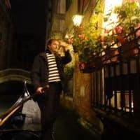 gondolier poles down narrow Venice canal italy