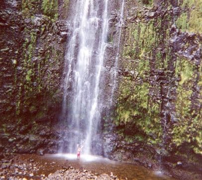 standing under waterfall in Hawaii