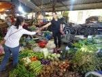 buying vegetables in her neighborhood market Vietnam