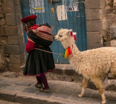 quechuan-woman-leads-llama-down-street-in-cusco-peru